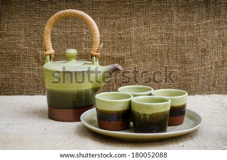 Green ceramic tea set on brownish sack