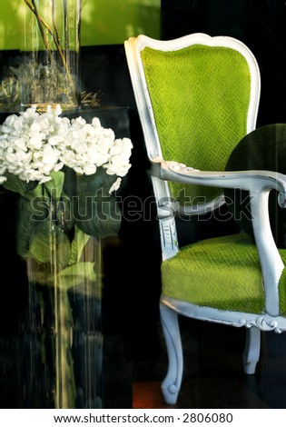 green chair and vase of flowers displayed in a store window - stock photo