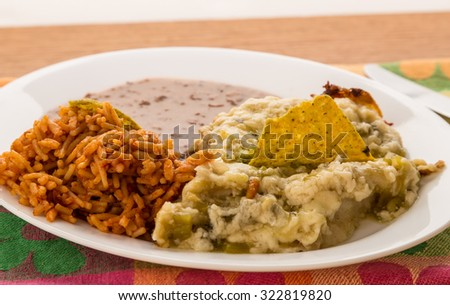 Green Chicken Enchiladas on Mexican Plate with refried beans and Spanish Rice. - stock photo