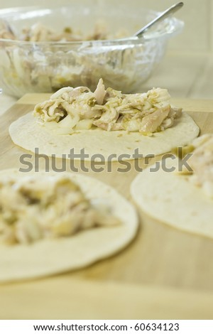 Green Chili Chicken Enchiladas Being Prepared - stock photo