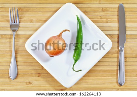 Green chili pepper and onion on a white plate and bamboo placemat with fork and knife