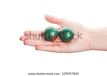 Green chinese balls in female hand isolated on white - stock photo