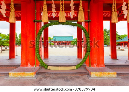 Green chinowa kuguri, a circular grass wreath for purification at entrance tower door into Heian-Jingu Shrine open to the inner courtyard and Taikyokuden main building in Kyoto, Japan. Horizontal