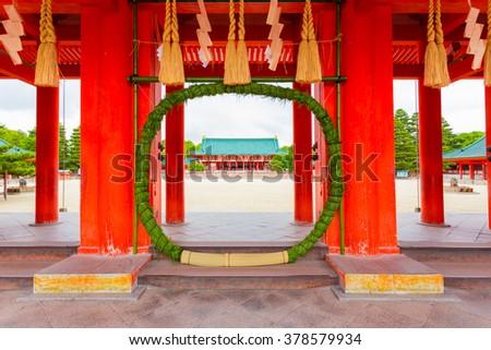Green chinowa kuguri, a circular grass wreath for purification at entrance tower door into Heian-Jingu Shrine open to the inner courtyard and Taikyokuden main building in Kyoto, Japan. Horizontal - stock photo