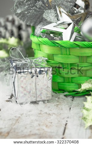 Green Christmas basket with silver toys on a white wooden background - stock photo