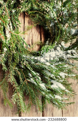 Green Christmas Natural Wreath with Snow on Branches on Wooden Background - stock photo