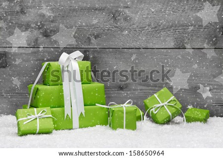 Green Christmas presents with snow on grey wooden background for a greeting card or coupon, voucher - stock photo