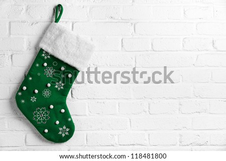 Green Christmas sock hanging on white brick wall - stock photo