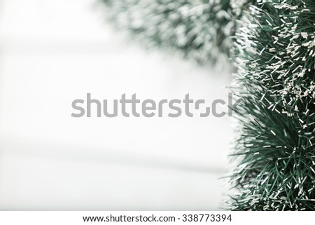 Green Christmas tinsel hanging with snow tipped ends
