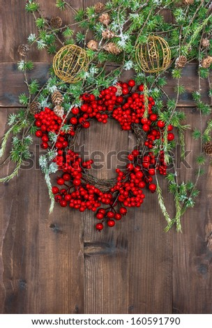 green christmas tree branches and wreath from red berries over rustic wooden background. festive home interior decoration