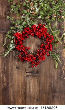 green christmas tree branches and wreath from red berries over rustic wooden background. festive home decoration