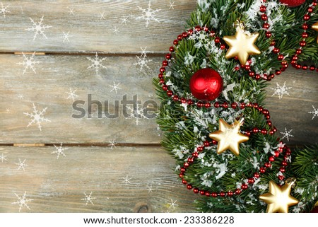 Green Christmas wreath with decorations on wooden background - stock photo