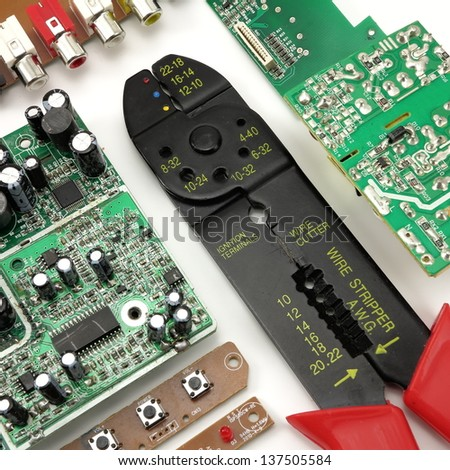 Green circuit board, wire stripper and electrical components - stock photo