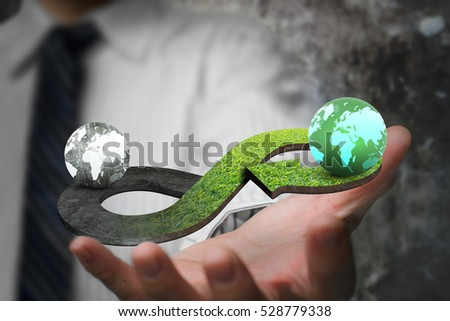 Green circular economy concept. Hand showing arrow infinity symbol with grass texture and two globes of different colors.