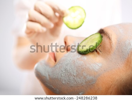 Green clay, cosmetic surgery, skin cleansing. Cosmetic procedure woman's face in the mask mitigating and cucumber slices on eyes  - stock photo
