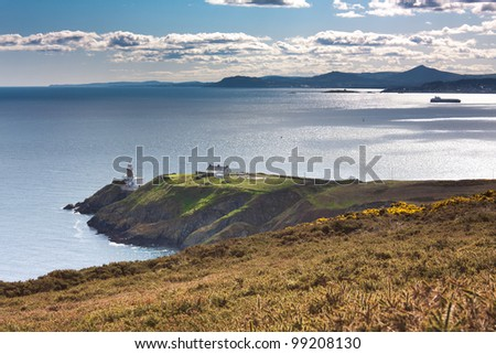 Green cliffs with a lighthouse and a ship anchored in a bay - stock photo