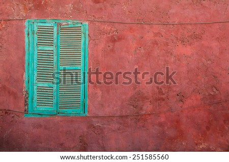 Green closed shutters on a dark pink, old wall - stock photo