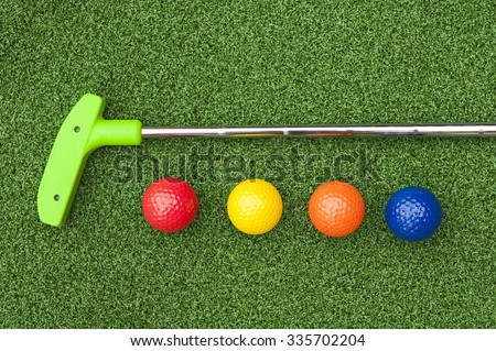 Green club and balls for putt putt on artificial turf - stock photo