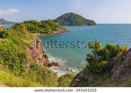 Green coastal rock in blue sea - stock photo