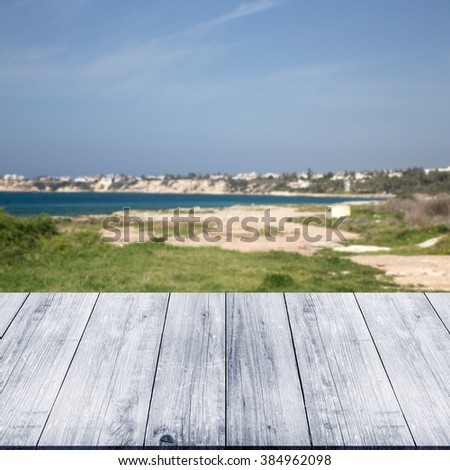 Green coastline and blue water of the Mediterranean Sea over old light wooden table or board. Blue sky like natural background. Collage. Selective Focus. - stock photo