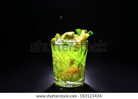 Green cocktail like mojito on dark background. With kiwi slices, mint and carambola. - stock photo