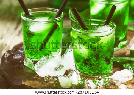 Green cocktail with mint, ice and soda, selective focus