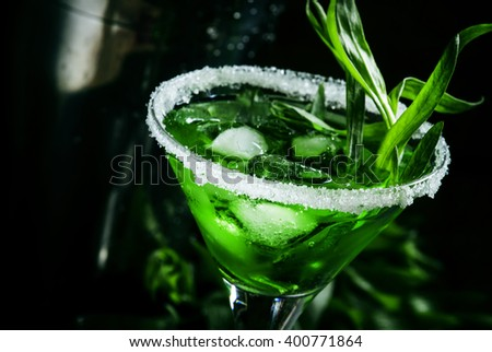 Green cocktail with tarragon and ice in martini glass on dark background with shaker, selective focus on the contents of the glass - stock photo