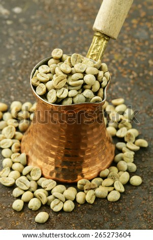 green coffee beans in a copper pot close-up, healthy food - stock photo
