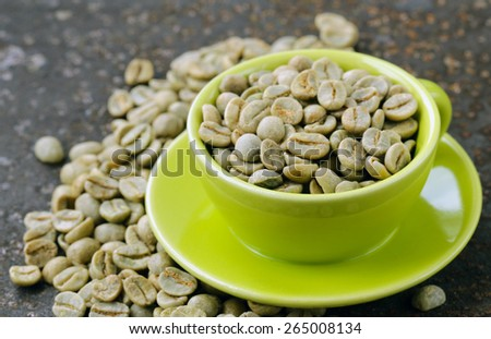 green coffee beans in a green cup close-up, healthy food - stock photo