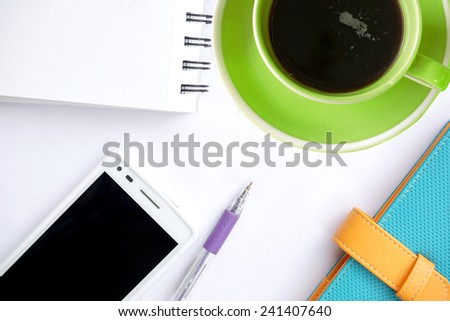 Green coffee cup and office supplies. View from above. Closeup on white background - stock photo