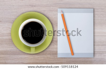 Green coffee cup, note book, on wooden table
