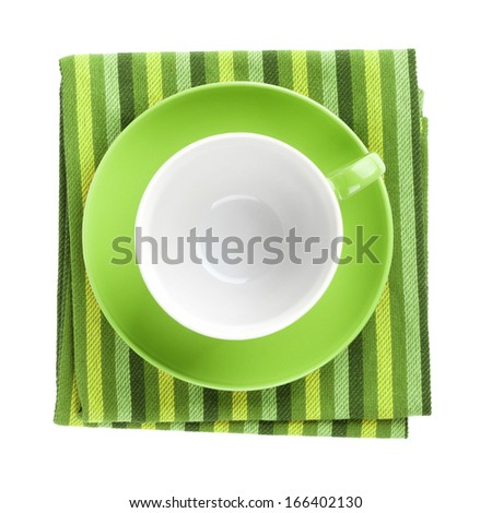Green coffee cup over kitchen towel. View from above. Isolated on white background - stock photo