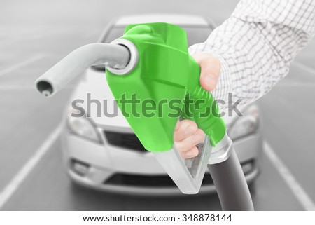 Green color fuel pump gun in hand with car on background - stock photo