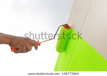 Green color painting wall with roller - stock photo