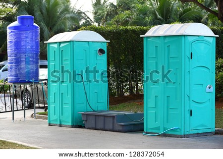 Green color Portable toilet with blue color water tank ready to service people for outdoor event - stock photo
