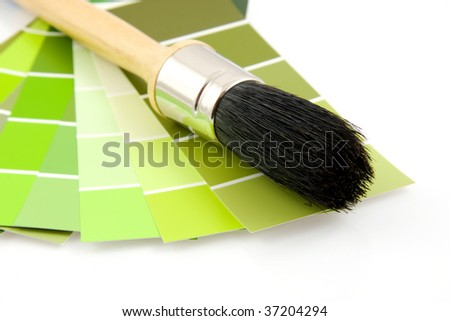 Green color samples and paint brush isolated on white background - stock photo