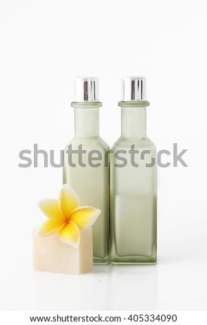 Green cosmetic bottle with soap bar and frangipani flowers - stock photo