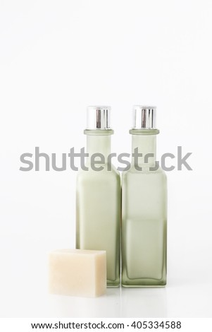 Green cosmetic bottles with soap bar on white background - stock photo