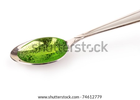 Green cough syrup in silver spoon
