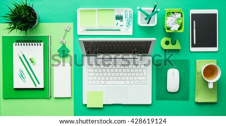 Green creative and eco-friendly desktop with laptop and office accessories, business and environmental care concept, flat lay - stock photo
