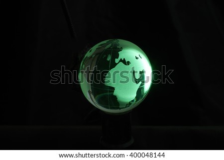Green crystal globe, isolated on black background. - stock photo