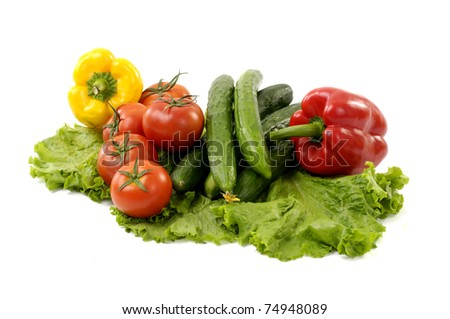 Green cucumber with red tomato and paprika on green lettuce