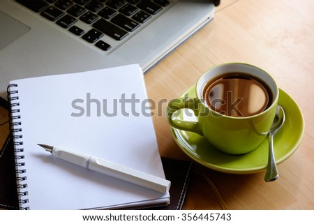 Green cup of Coffee with note book.