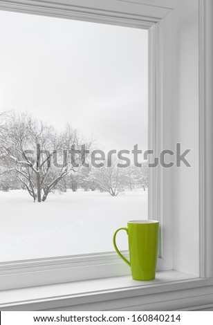 Green cup on a windowsill, with winter landscape seen through the window. - stock photo