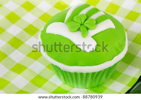 Green cupcake with head and shamrock for Saint Patrick's day - stock photo