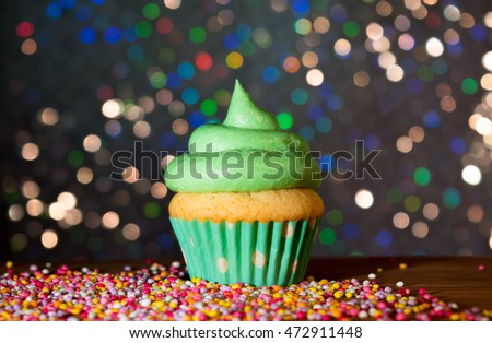 Green cupcake with swirl frosting and sprinkles with a bokeh background