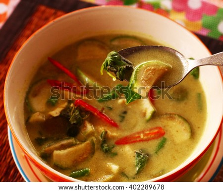 green curry thai soup with chicken and red hot chily pepper spicy in bowl with spoon - stock photo