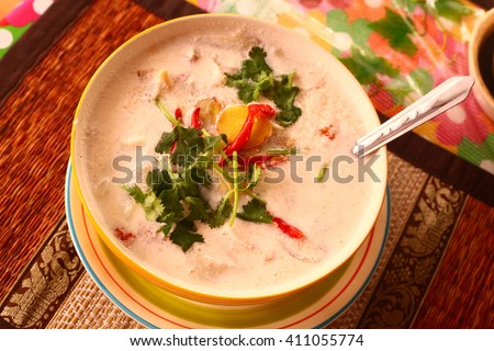 green curry thai soup with sea food coconut milk cream and red hot chilly pepper spicy in bowl with spoon - stock photo