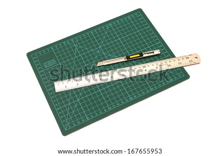 Green cutting mats with iron ruler and cuter isolated on white background