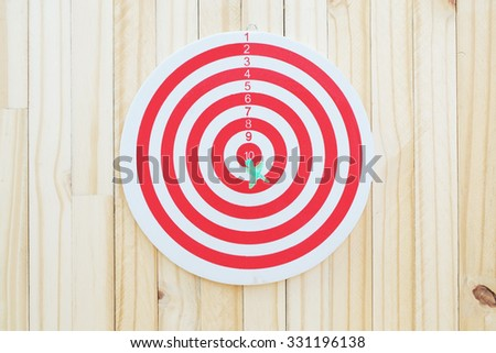 Green dart thrown at ten point on dartboard which is shown one to ten points on wood wall - stock photo